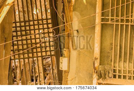 Interior of abandoned shack with wood lattice windows and an old electrical outlet attached to a piece of wood
