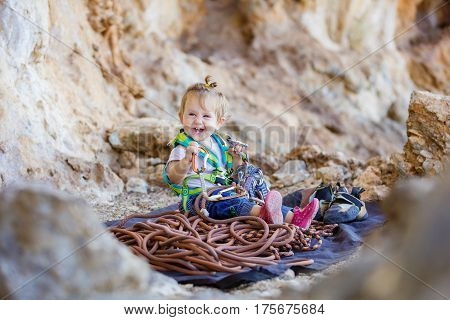 Happy little girl wearing safety harness and playing with rock climbing equipment