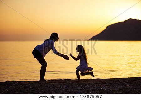 Mother and daughter having fun on beach at sunset