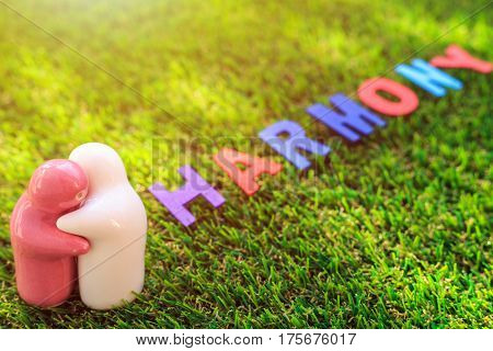 White And Pink Ceramic Doll On Green Grass With Wood Text