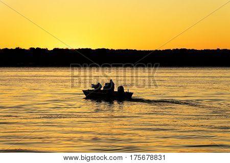 Fishermen boating into the golden sunrise on a reflective lake.