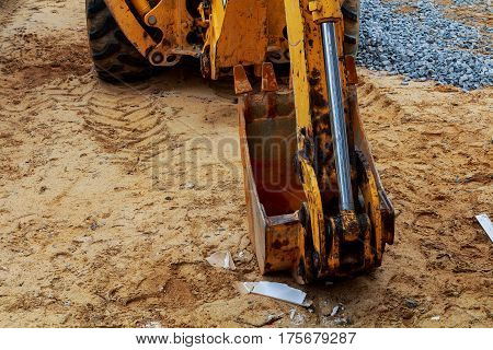 Yellow excavator loader at construction site with raised bucket