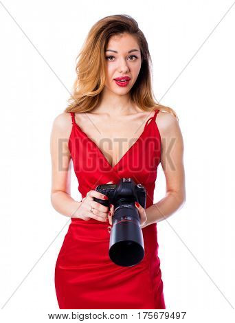 Happy blonde photographer woman in sexy red dress holding camera, isolated on white background