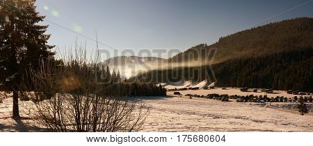 Cars parked in the mountains. Winter morning - Carpathian hills. Fog is lit by the sun. Panorama.