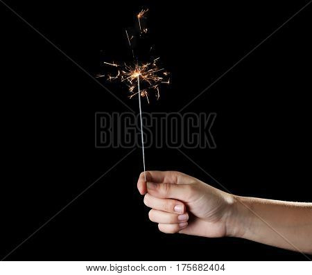Female hand holding sparkler on dark background