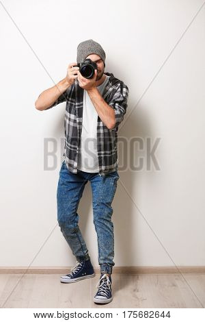 Handsome young photographer on light wall background