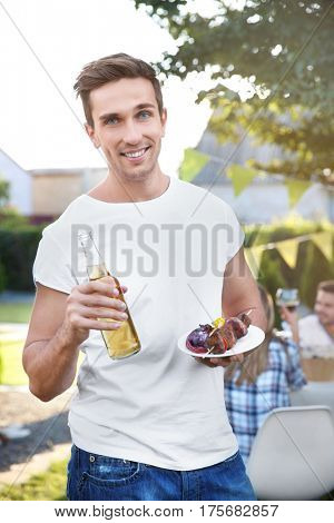 Young man holding bottle of beer and plate with grilled meat and vegetables