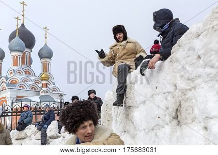 Berdsk Novosibirsk oblast Siberia Russia - February 26 2017: Russian holiday of farewell to winter. Snow sport games of young people at an Orthodox Church. The storming of a snow fortress