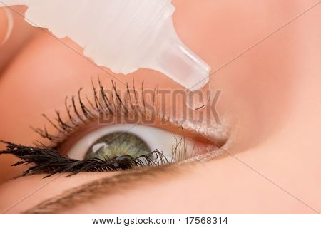 Closeup of eyedropper putting liquid into open eye. Top view
