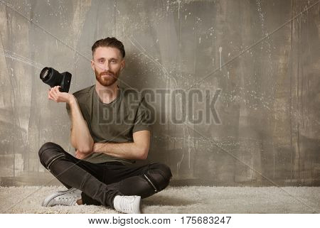 Handsome photographer sitting on floor near grunge wall