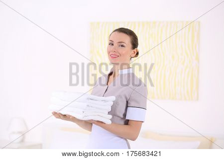 Attractive chambermaid holding pile of clean towels in the room