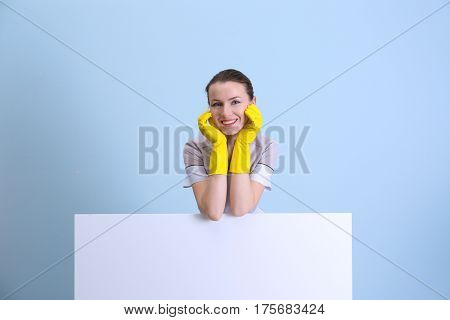 Beautiful chambermaid in uniform on color background