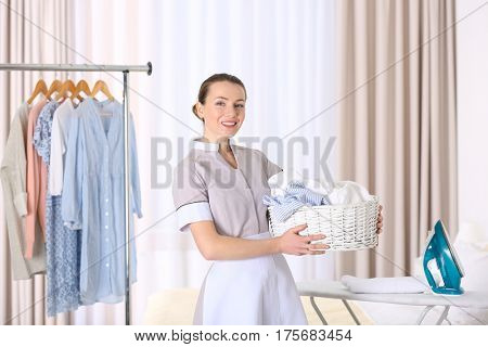 Chambermaid holding basket with laundry in hotel room