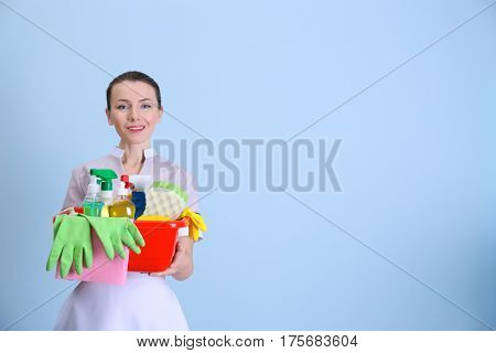 Beautiful chambermaid with cleaning equipment on color background