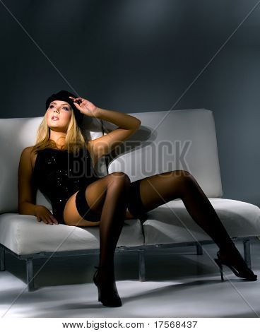 Perfect young model in black on white couch studio portrait
