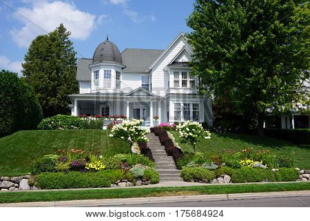 HARBOR SPRINGS, MICHIGAN / UNITED STATES - August 4, 2016: A beautiful home with a corner turret, near the waterfront on Bay Street in Harbor Springs, Michigan.