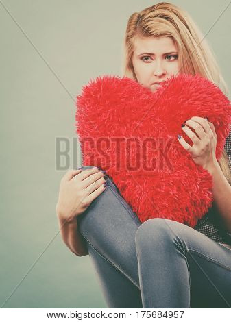 Sad Woman Holding Red Pillow In Heart Shape