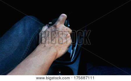 Dry skin hand with gear old man driving car alone
