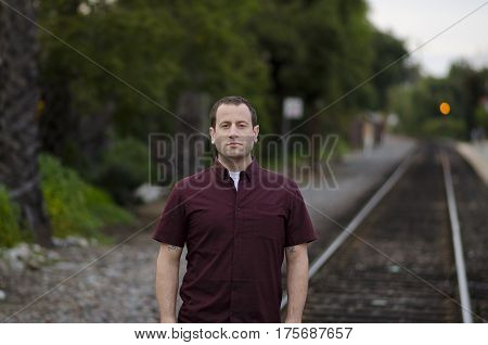 Man with a serious stern expression standing on the railroad tracks alone.