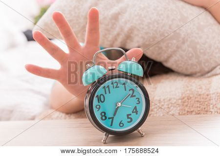 Woman laying in the bed with pillow on her head and reaching the alarm clock to turn it off