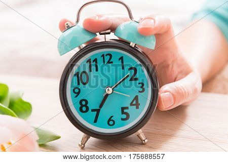 Hand on alarm clock trying to turn it off