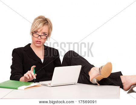 Beautiful businesswoman with laptop, legs over table