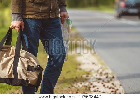 Man with map and bag in hand walking on a roadside. Hitchhiking concept
