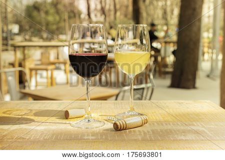 Two vibrant glasses of red and white wine with an old corkscrew and a cork on a sunlit table of a summer restaurant terrace, on a blurred background. Slightly toned image