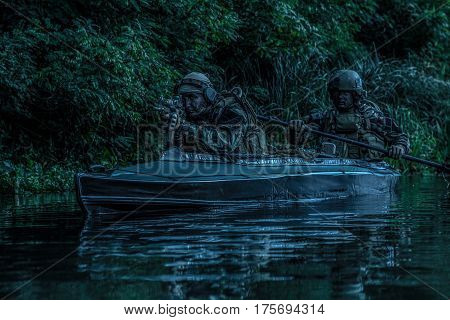 Special forces men with painted faces in camouflage uniforms paddling army kayak. Boat moving calmly across the river, diversionary mission, twilight