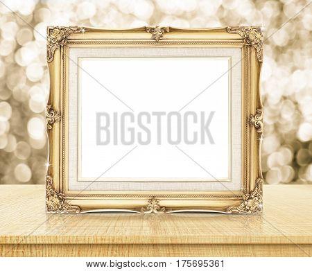 Blank Victorian Style Golden Frame With Sparkling Gold Bokeh Wall And Wooden Table, Business Concept