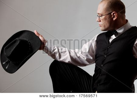 Handsome muscular male looking at his hat