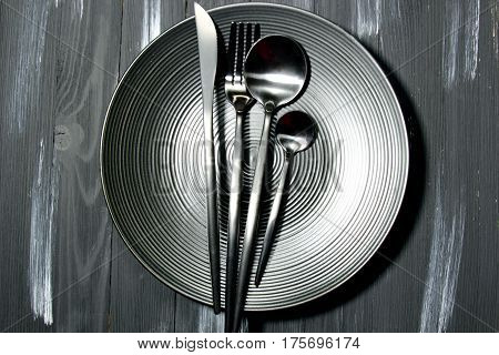 A black plate with cutlery on a wooden background top view.