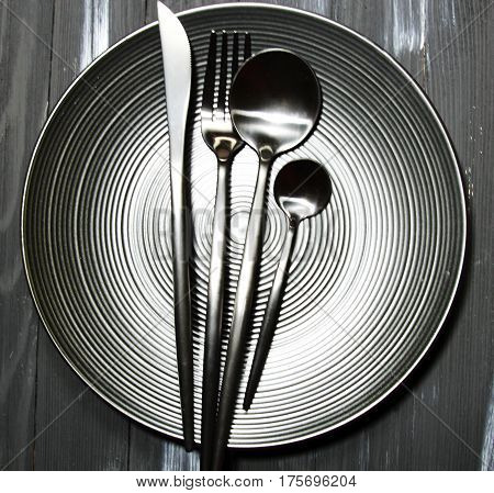 A black plate with cutlery on a wooden background with copy space top view.
