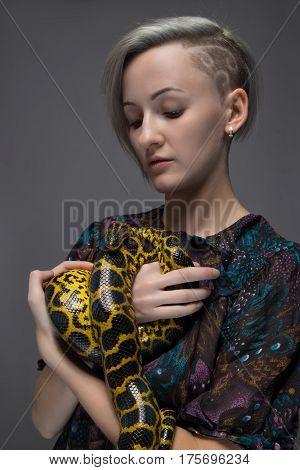 Blond woman holding snake on gray background