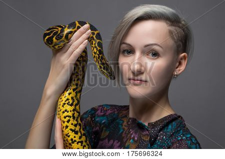 Blond woman holding yellow anaconda on gray background