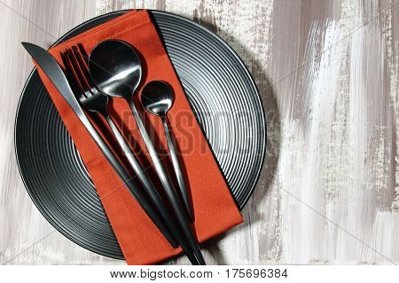A black plate with fork spoon knife cutlery on a red napkin top view.