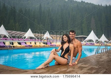 Happy Beautiful Couple Sitting On The Edge Of Swimming Pool In The Luxurious Resort. On The Backgrou