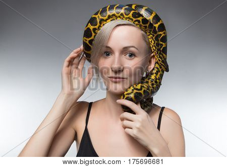 Blond woman and snake on her head on gray background
