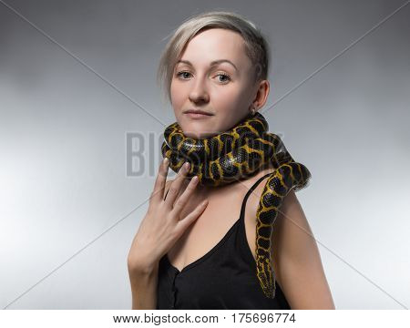 Woman and snake on her neck on gray background