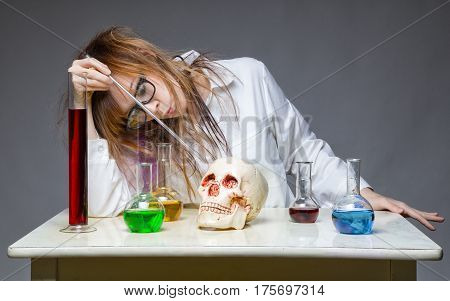 Working chemist with human skull on gray background