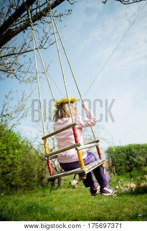 Child with dandelion wreath swnging on seesaw hanging from tree in backyard - rear view