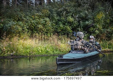 Special forces men with painted faces in camouflage uniforms paddling army kayak. Boat moving across the river, diversionary mission, copy space
