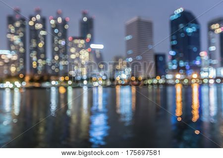 Night blur bokeh light city office building with water reflection abstract background