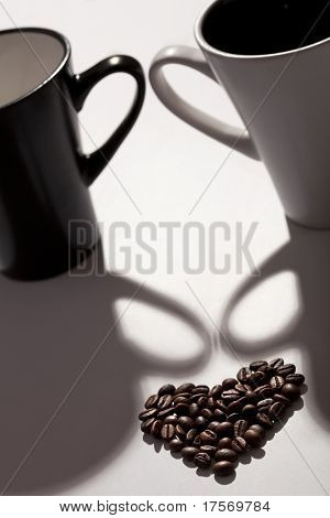 Various coffee beans in the shape of a heart against two cups, black and white