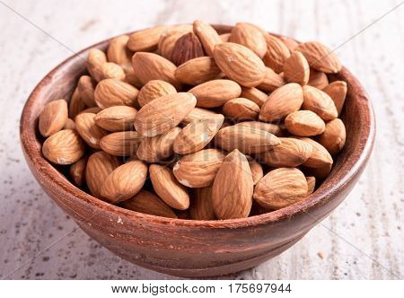 Almond on the clay pot , wooden background