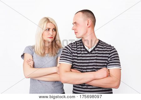 Offended couple standing with crossed arms in studio and looking at camera.
