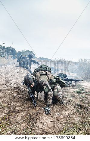 Squad of elite french paratroopers of 1st Marine Infantry Parachute Regiment RPIMA in action in enemy trenches one militant jumping out