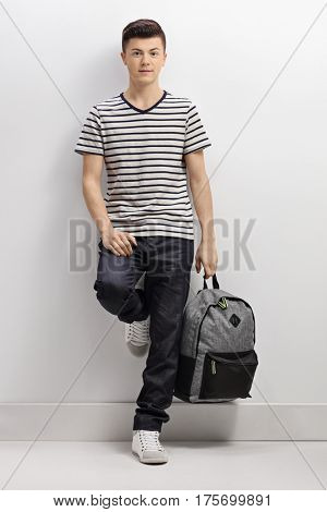 Full length portrait of a teenage boy holding a backpack leaning against a gray wall