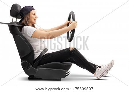 Profile shot of a teenage girl sitting in a car seat and holding a steering wheel isolated on white background