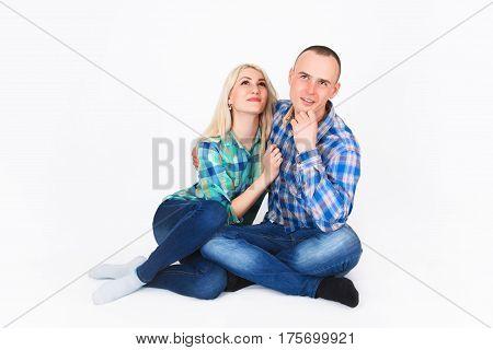 Romantic young couple sitting on floor cuddling in studio.